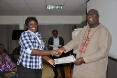 A lady participant receiving her certificate from Mr. Francis Dadzie, Execuive Director of AAG