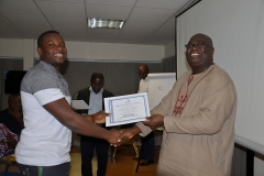 A male participant receiving his certificate from Mr. Francis Dadzie