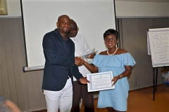 A female participant receiving her certificate from Mr. Clarence Nartey, the Resource Person