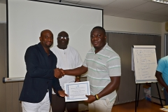 Mr. Francis Dadzie, the Executive Director helping the Resource Person, Mr. Clarence Nartey to present certificate to a participant